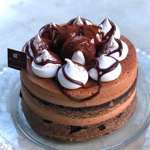 A layered Chocolate Mud Cake filled and topped with chocolate buttercream, meringues and drizzled with chocolate ganache sauce.