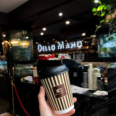 A hand holding a take away coffee cup with neon sign that says Dello Mano