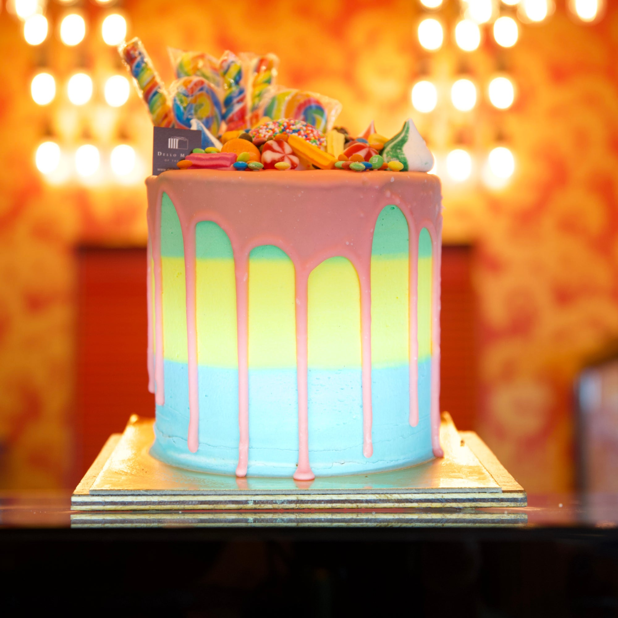 Birthday Cake with Pink drips and rainbow frosting topped with lollies