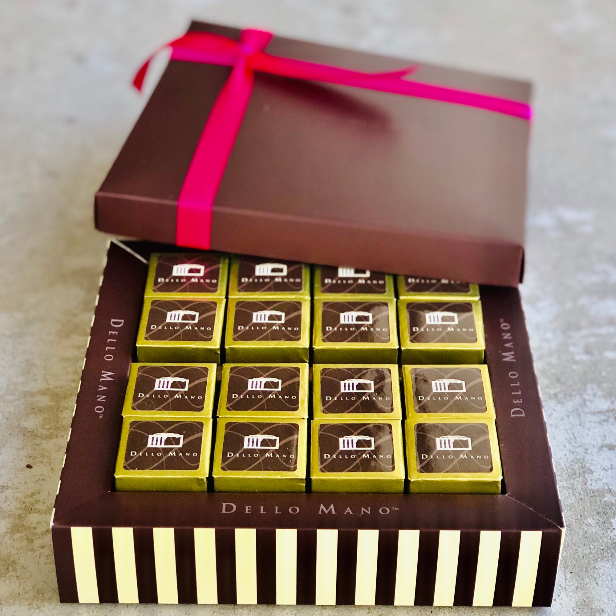 Sixteen gold brownie cubes with brown stickers that say Dello Mano and lid with pink ribbon