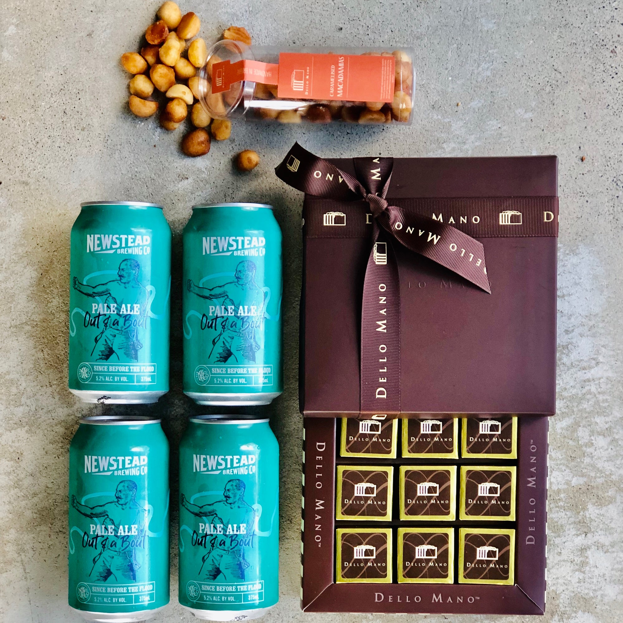 Open Brownie Gift Box with 4 cans of beer and open tube of macadamia nuts spilling onto concrete