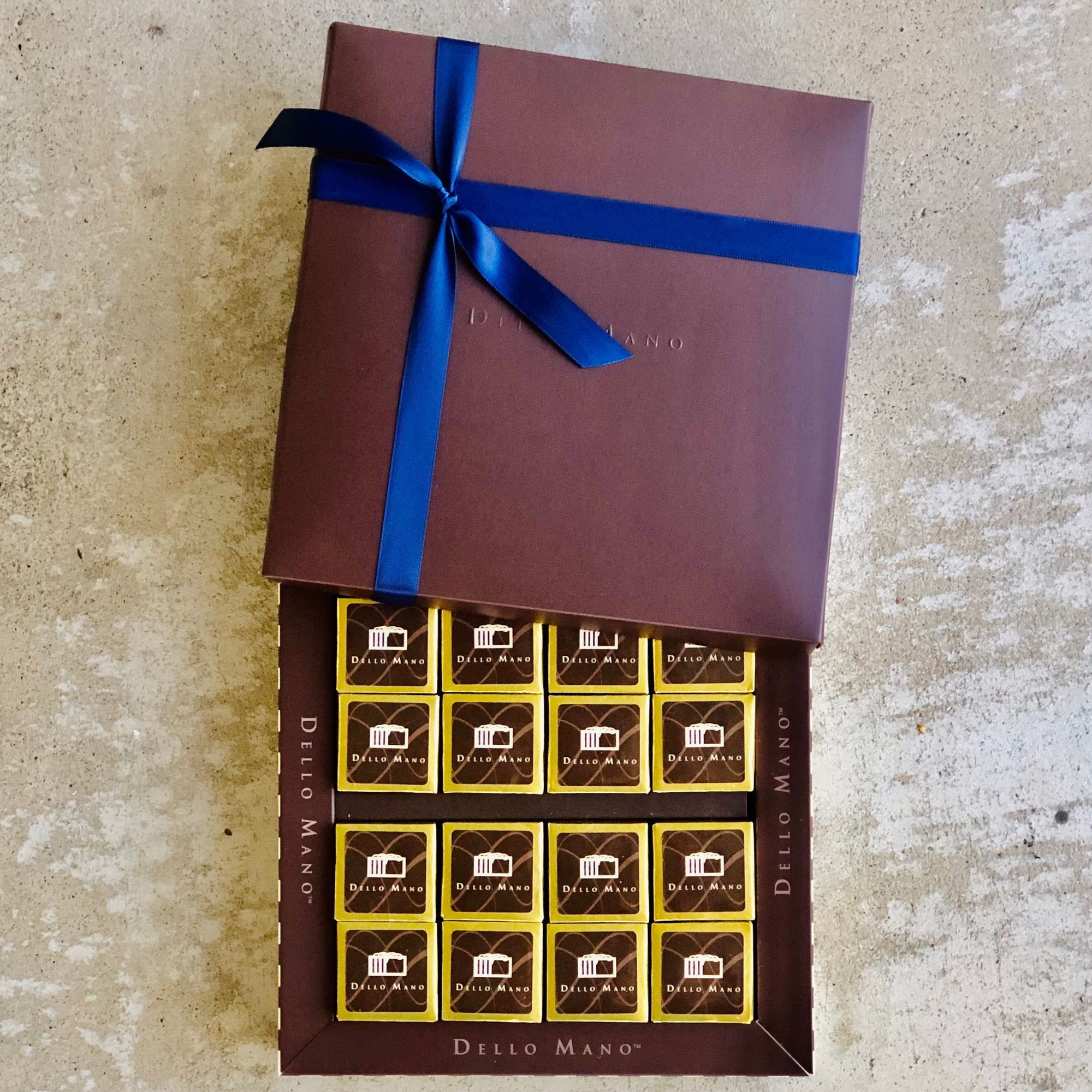 Sixteen brownies in a chocolate gift box with blue ribbon