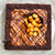 A view looking down on a caramel filled brownie tart with roasted gold macadamia nuts