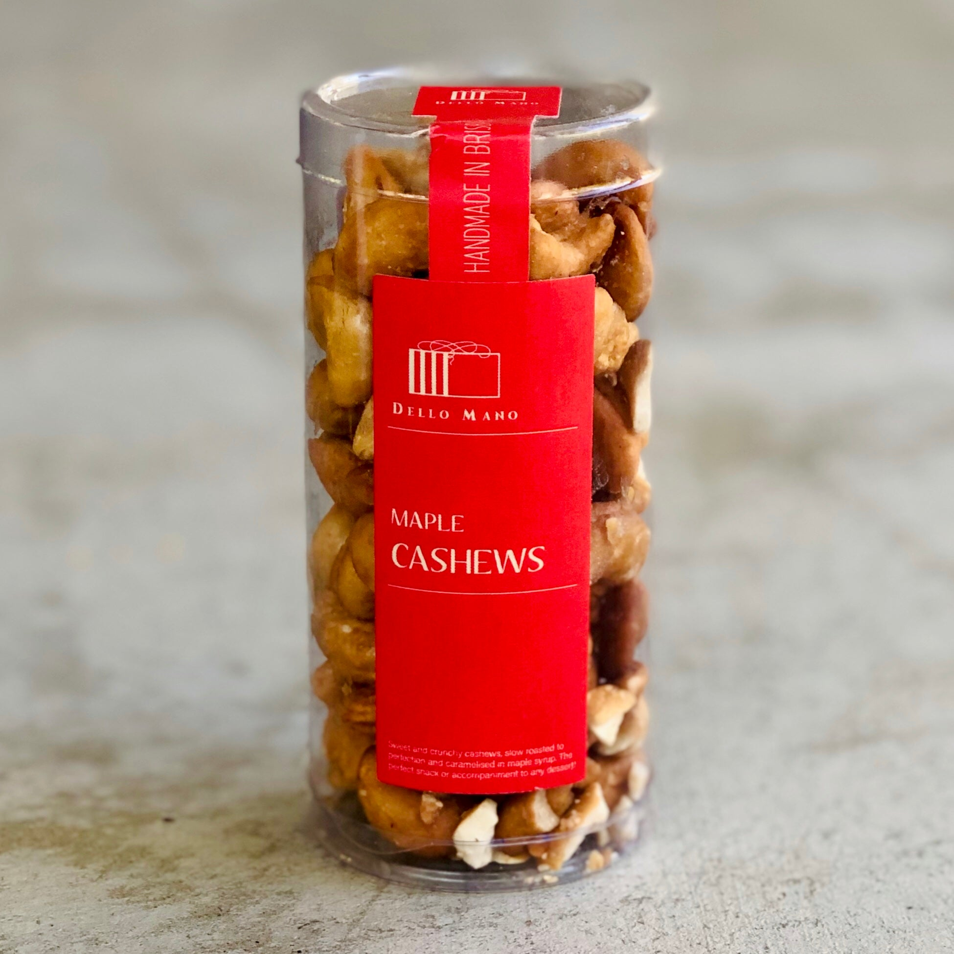 A tube of Maple Caramelised Cashews with red label on concrete base