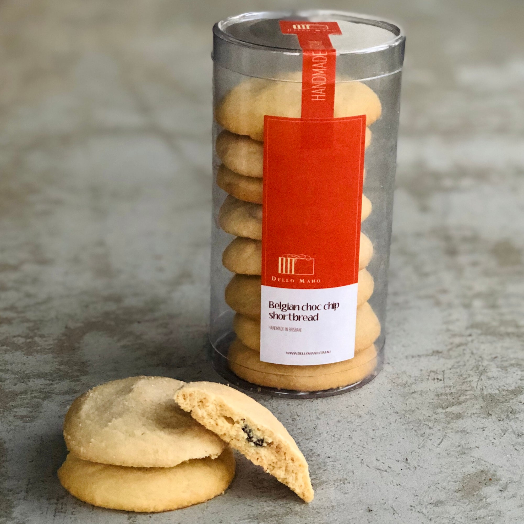 A broken open Chocolate Chip Shortbread cookie in front of a tube of handmade cookie gift