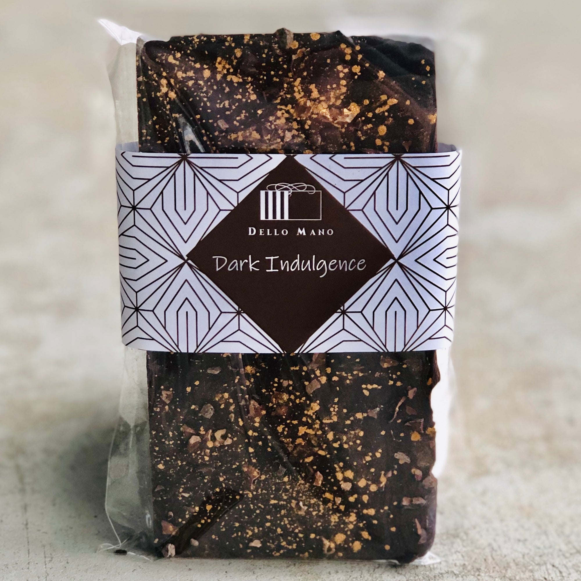 A dark chocolate bar with gold dust and cocoa nibs