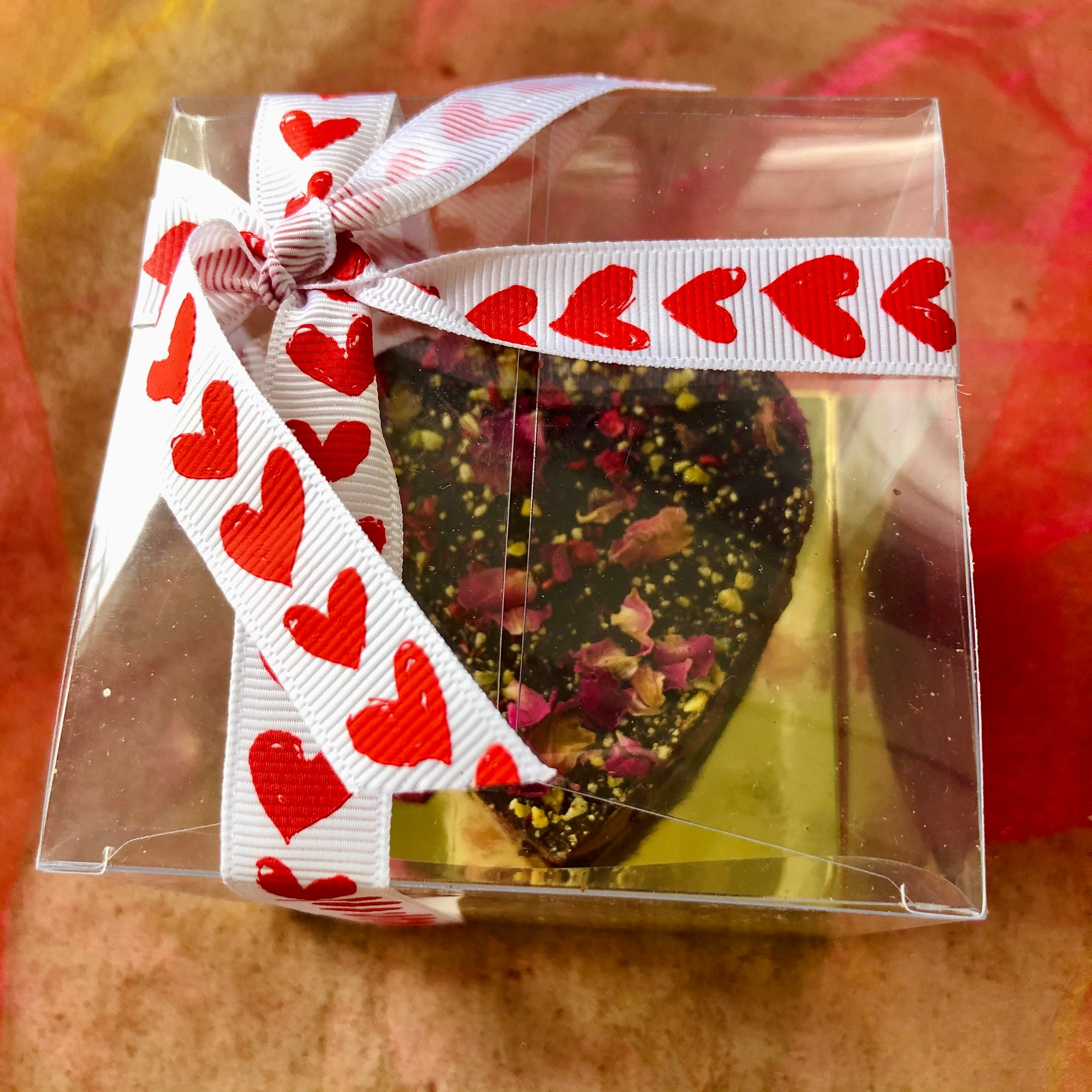 A  Valentine Chocolate Heart sprinkled with rose petals and kibbled pistachios