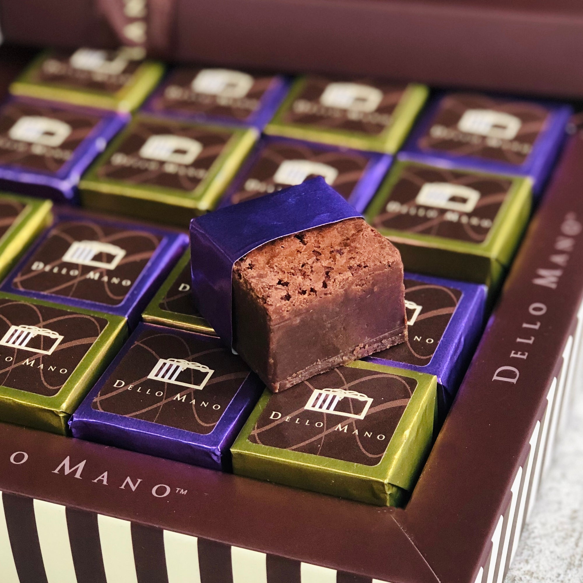 An open gift box of brownies with an purple foiled open brownie on top