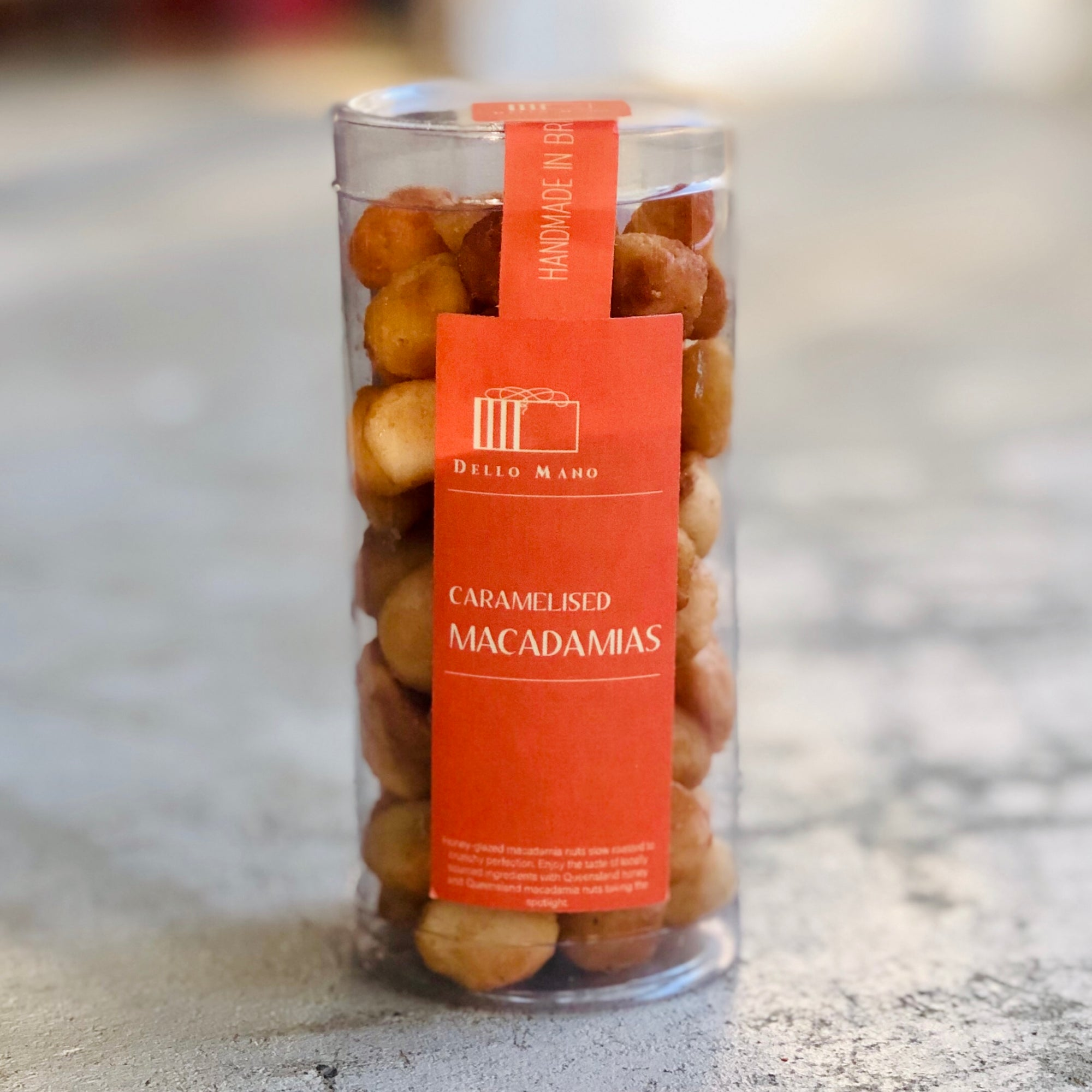 A tube of Honey Caramelised roasted Macadamias with orange label