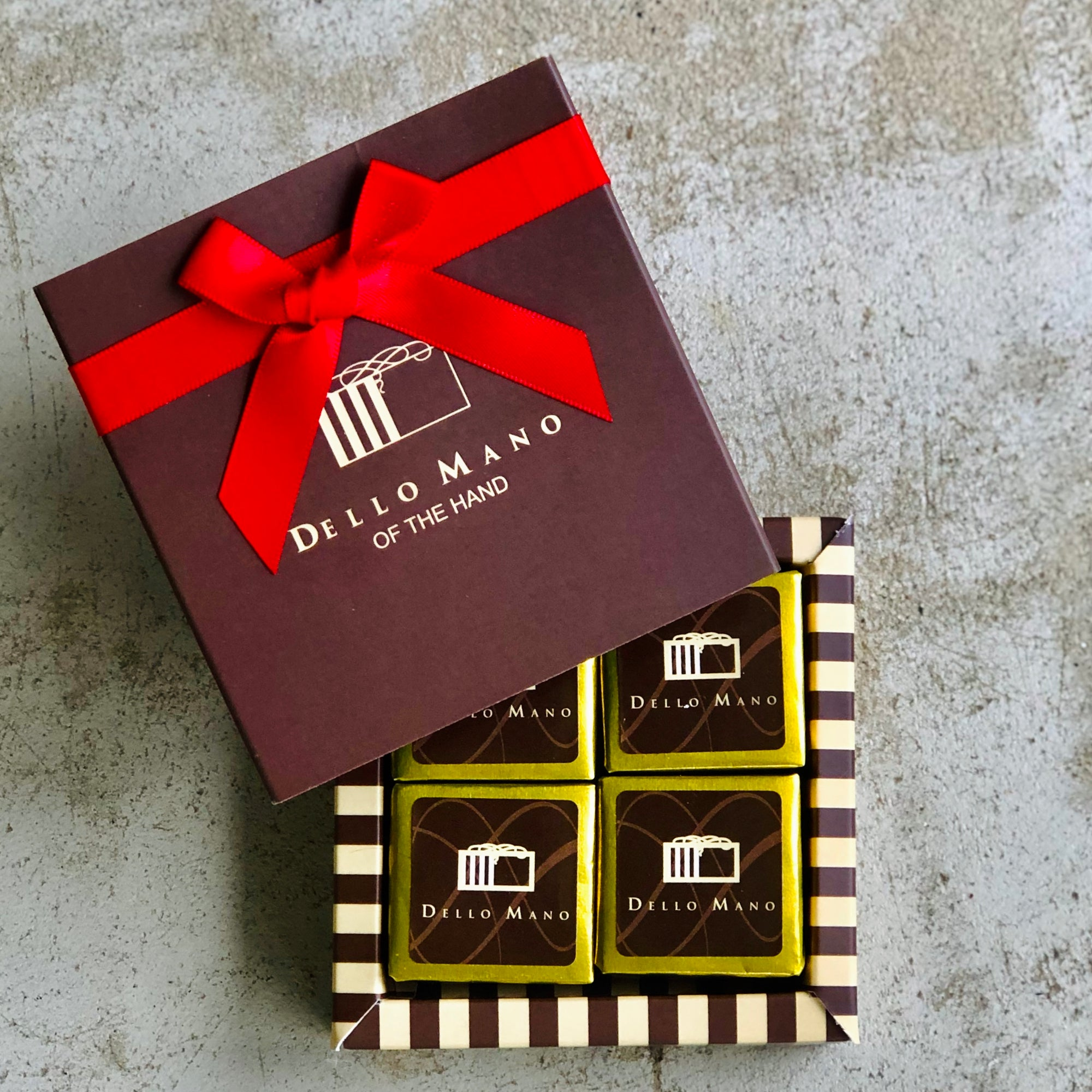Four brownie cubes in a gift box with lid saying Dello Mano brownies
