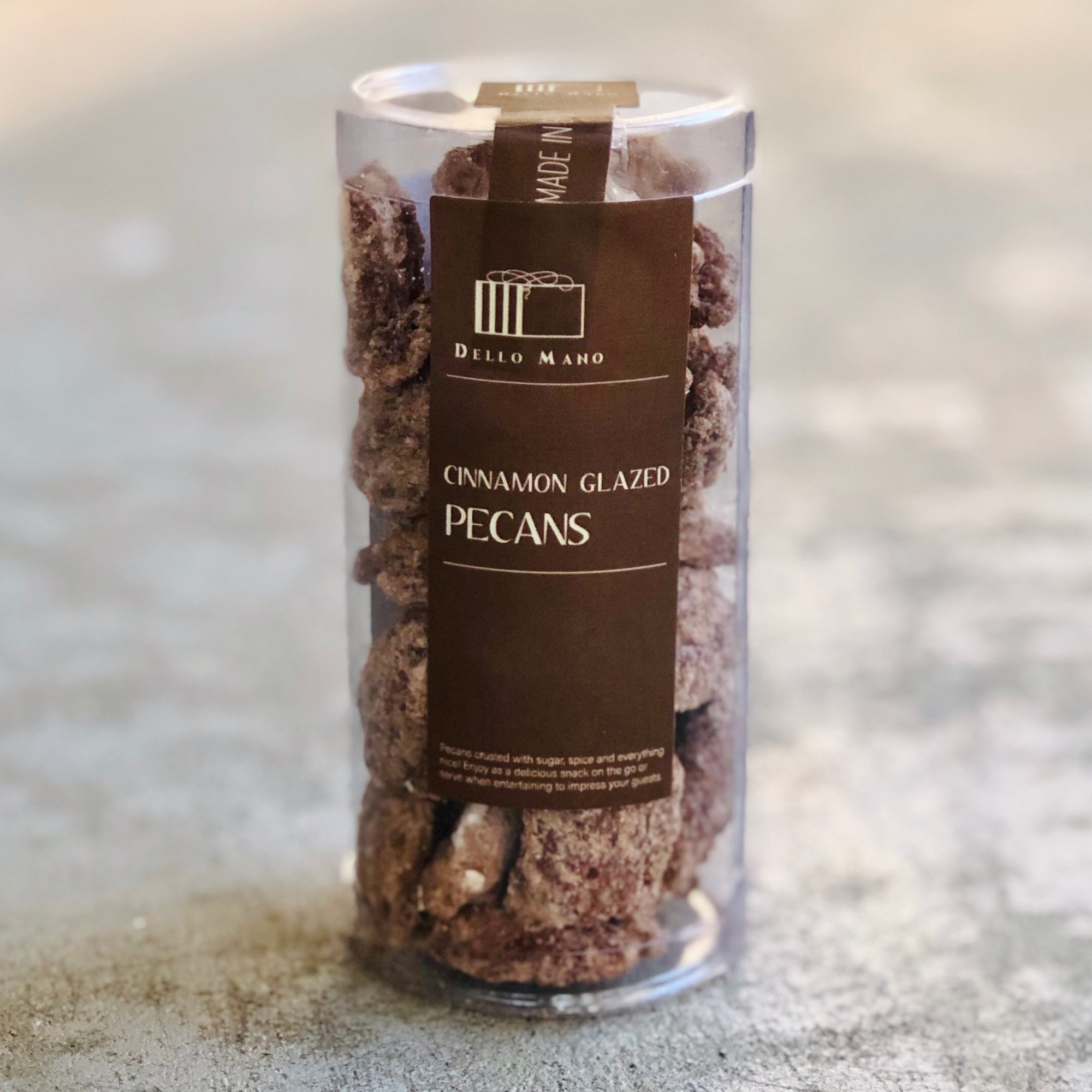 A tube of glazed pecan nuts with brown label and Dello Mano logo