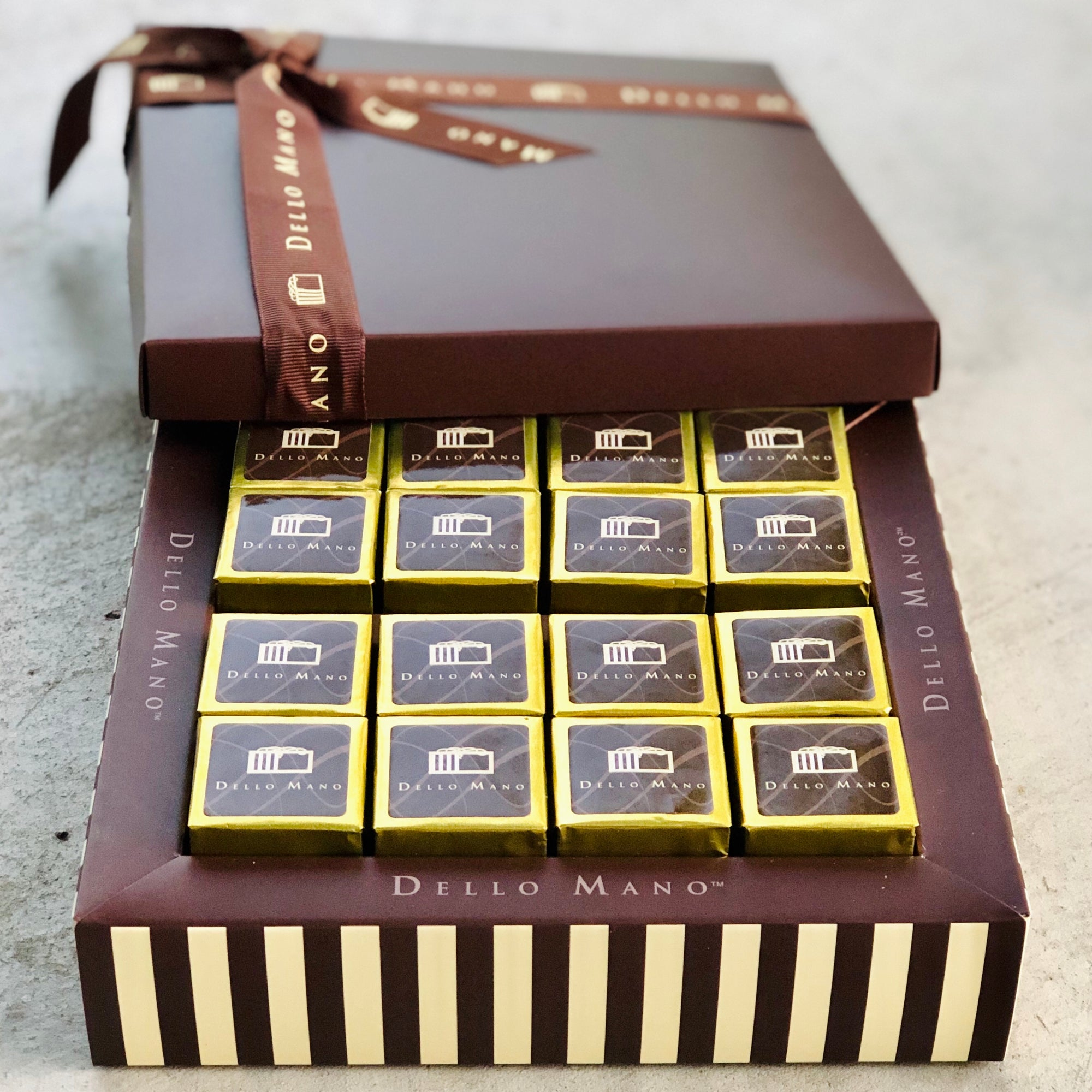 A brownie gift box filled with gold foiled cubes of brownie with open brownie on top