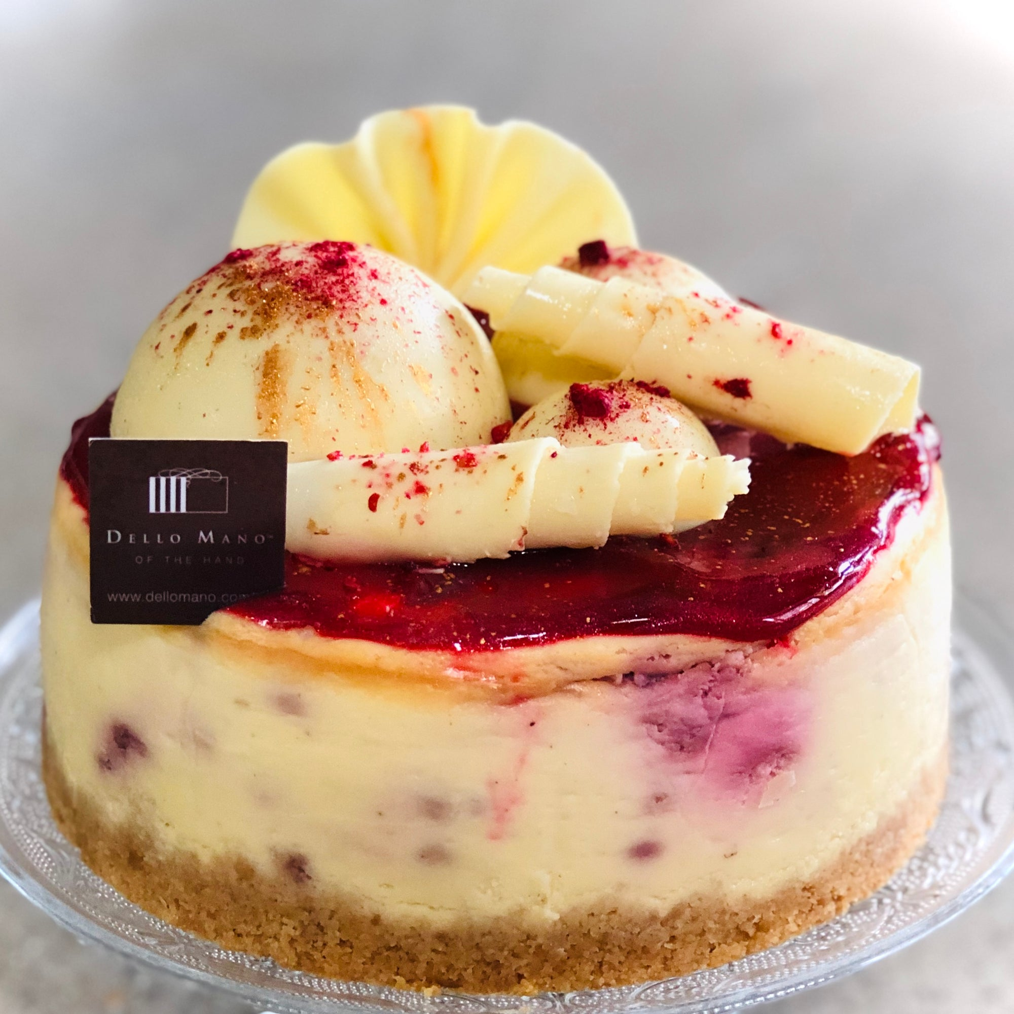 A raspberry white chocolate cheesecake decorated with Belgian White Chocolate decorations