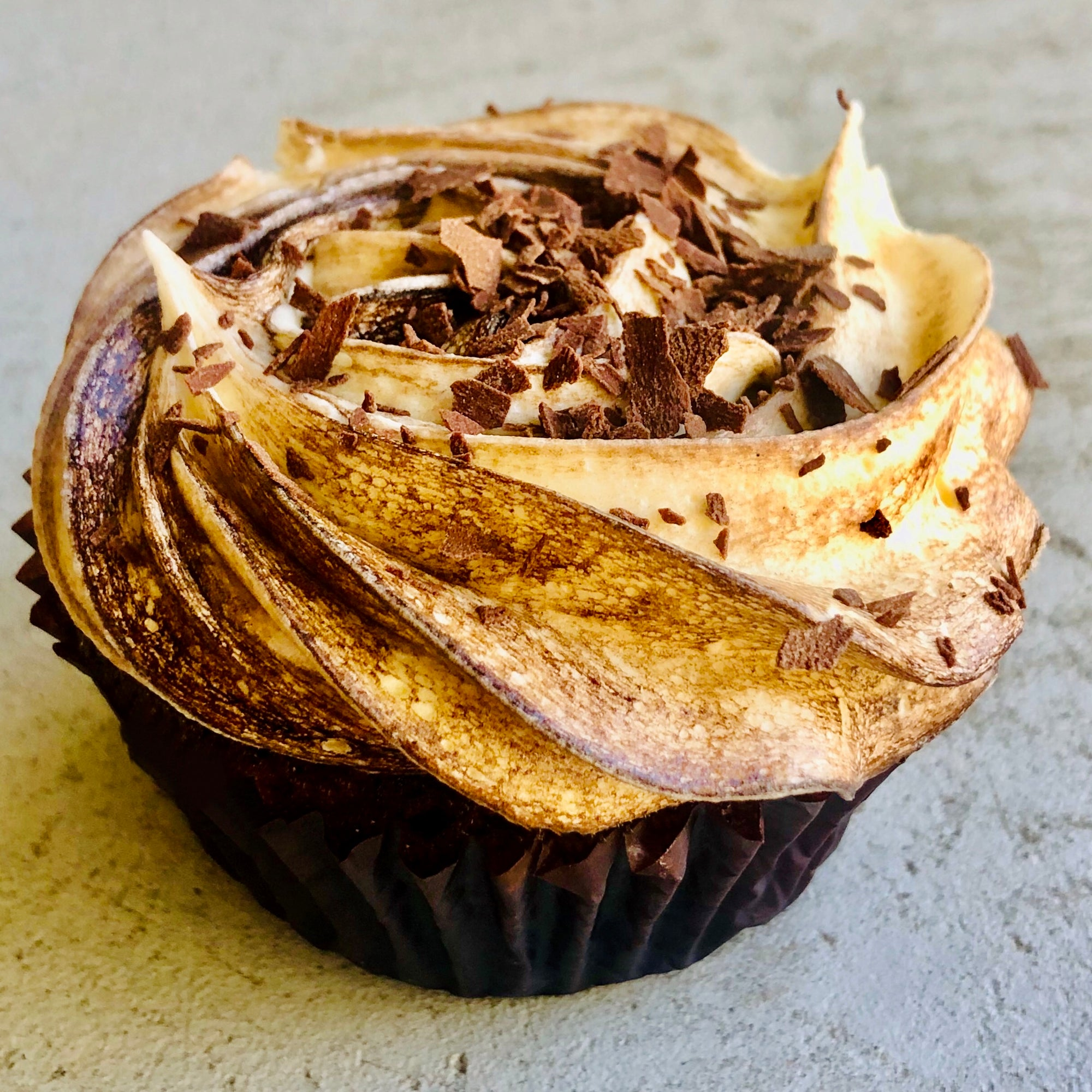 Chocolate cupcake with swirled chocolate and vanilla butter cream and sprinkled with chocolate crumb