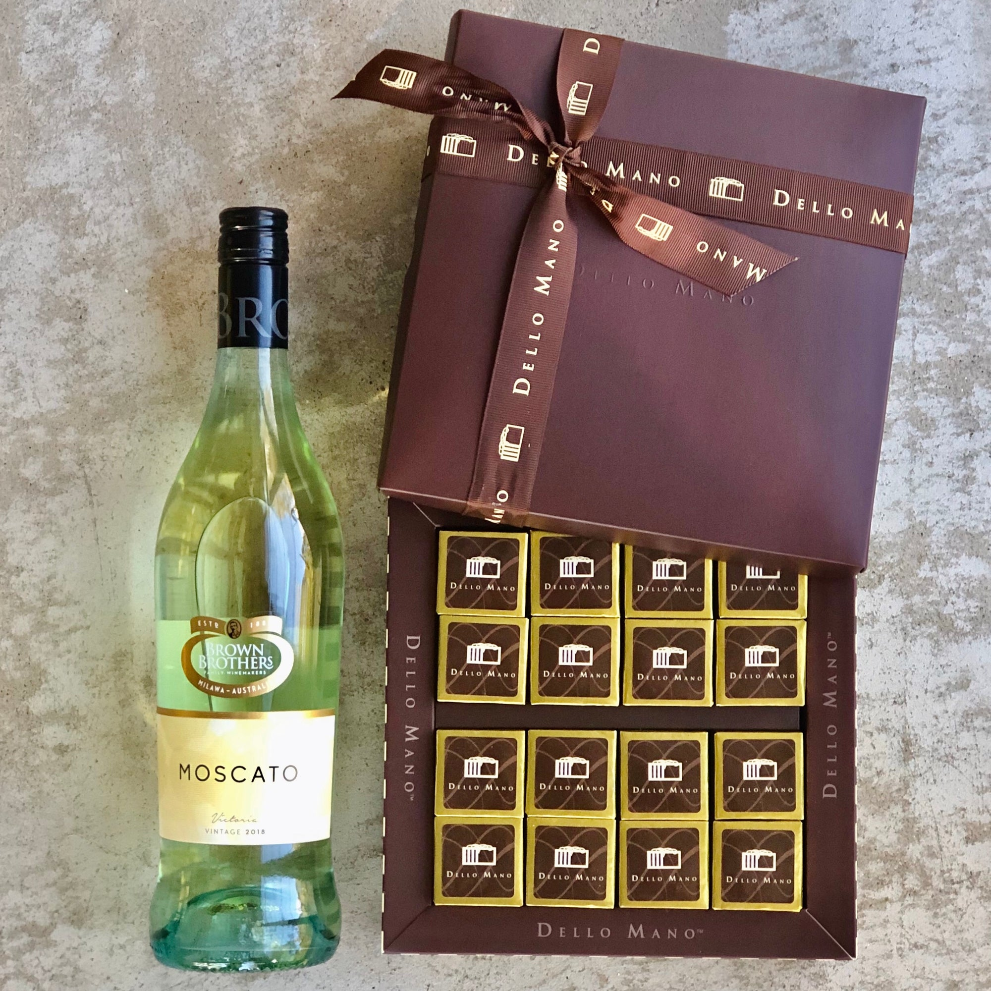 A brownie hamper delivery of brown gift box and bottle of sweet moscato wine