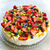 A beautiful pavlova topped with a medley of fresh fruits like strawberry and blueberry
