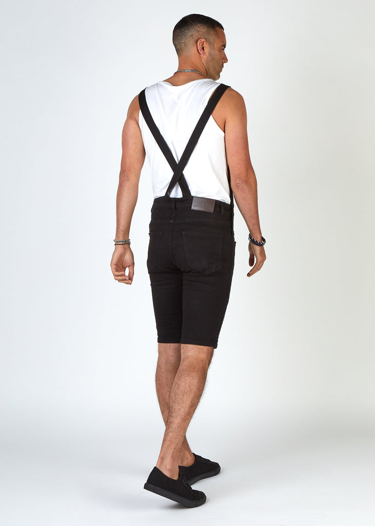 Rear pose to highlight slim overall straps that cross over at the back of Trafford biker dungaree shorts