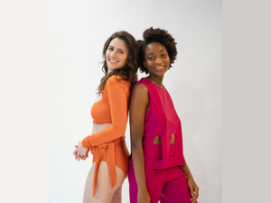 Raelle and Nechama back to back in the magenta Marije cutout set and burnt orange Lydia set, in white background.