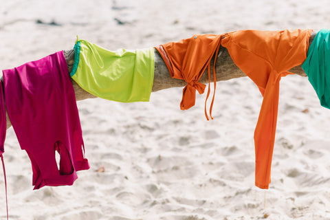 MIGA Swimwear tops, bottoms and skirts over branch at the beach.