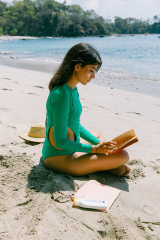 Model wearing Anna One Piece reading book at beach