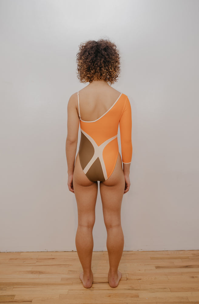 Model facing back wearing orange, brown and creme one-piece with X design at back.