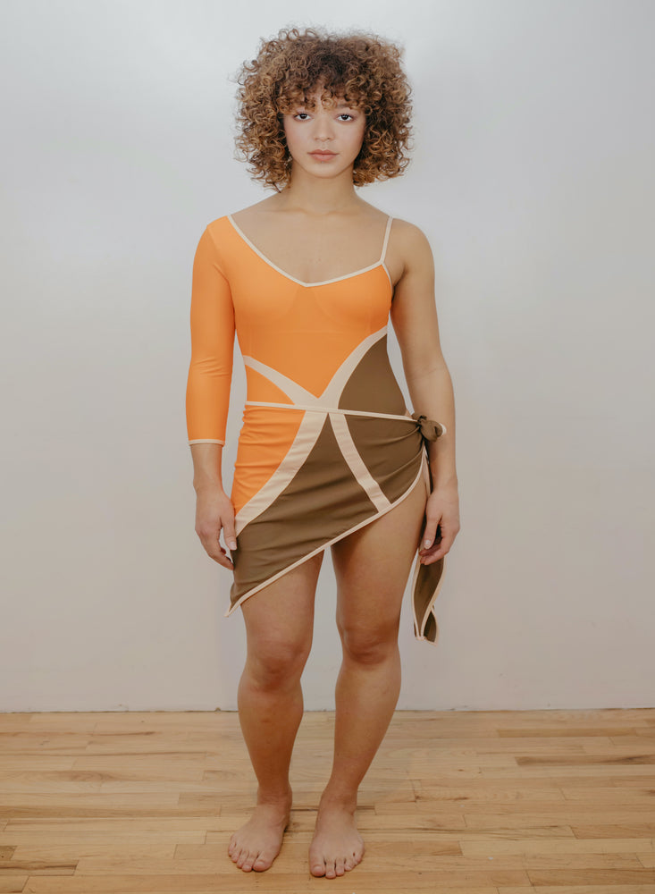 Model wearing orange, brown and creme one piece with X design in front. Wearing matching sarong.