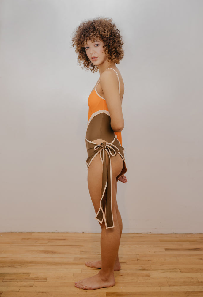 Model to the side wearing orange, brown and creme one piece with X design in front. Wearing matching sarong.