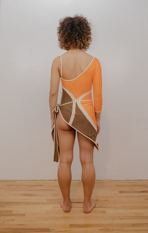 Model facing back wearing orange, brown and creme one piece with X design in front. Wearing matching sarong.