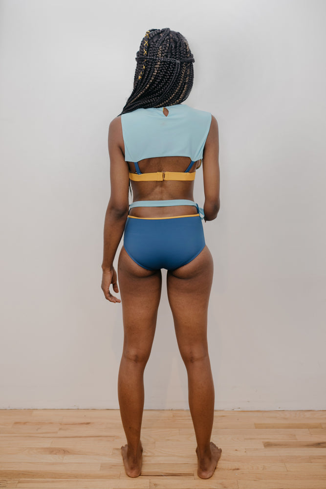 Model facing back wearing blue, yellow and light blue bikini.