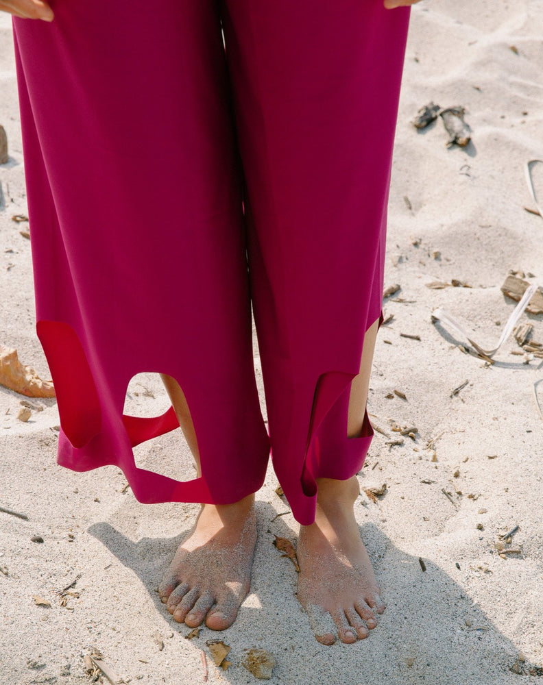 Model showcasing arc cutouts of magenta high waisted pants. Feet in sand.