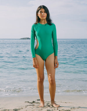 Model with ocean in the back. She is wearing long sleeves rashguard in emerald green. Circular cutout at right side of torso. Zipper with pulley at back.