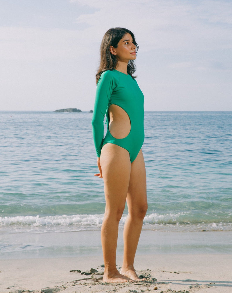 Model looking to the side with ocean in the back. She is wearing long sleeves rashguard in emerald green. Circular cutout at right side of torso. Zipper with pulley at back.