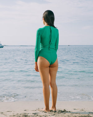 Model looking back to the ocean. She is wearing long sleeves rashguard in emerald green. Circular cutout at right side of torso. Zipper with pulley at back.