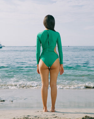 Model looking back to the ocean, hair to side. She is wearing long sleeves rashguard in emerald green. Circular cutout at right side of torso. Zipper with pulley at back.