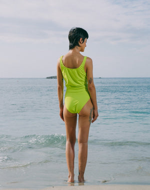 Model looking at ocean wearing lime green tankini top with scoop neck that comes with a front pocket with emerald green detail. She is also wearing matching lime green high-waisted bikini bottom with moderate coverage.