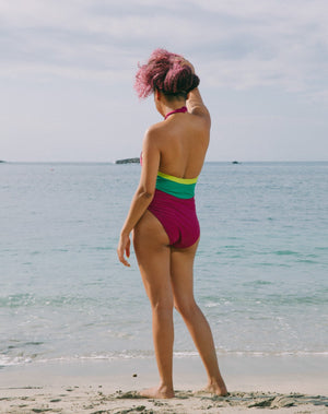 Model looking to side, hair up, with ocean at back wearing magenta halter one-piece swimsuit with lime green details at sides. Decorative button detail at front. Long tying magenta strings for multiple uses.