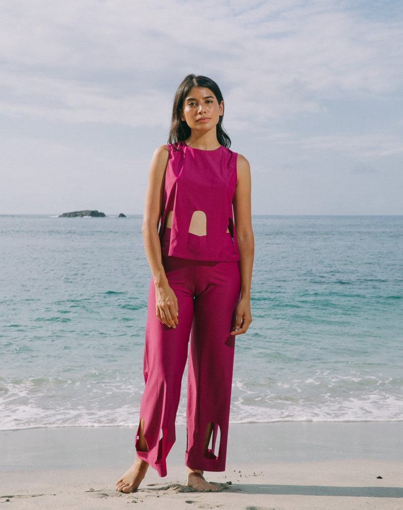 Model with ocean at back wearing magenta high waisted pants with arc cutouts around legs. Slight bell bottom leg. Also wearing magenta color short sleeve top with scoop neck. Arc cutouts around waist. Loose fit.
