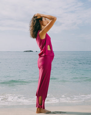 Model with ocean at back, looking to the side with hands on head. She is wearing magenta high waisted pants with arc cutouts around legs. Slight bell bottom leg. Also wearing matching magenta color short sleeve top with scoop neck. Arc cutouts around waist. Loose fit.