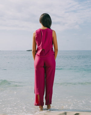 Model facing the ocean is wearing magenta high waisted pants with arc cutouts around legs. Slight bell bottom leg. Also wearing matching magenta color short sleeve top with scoop neck. Arc cutouts around waist. Loose fit.