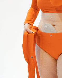 Closeup of model showing her stoma bag in torso, wearing burnt orange high-waisted bikini bottom with unsnapped belt and burnt orange long sleeves top.