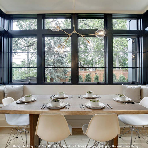 _hover brass reef globe chandelier dining room scene big windows Detail Homes Chris Van Klei Ben Richter