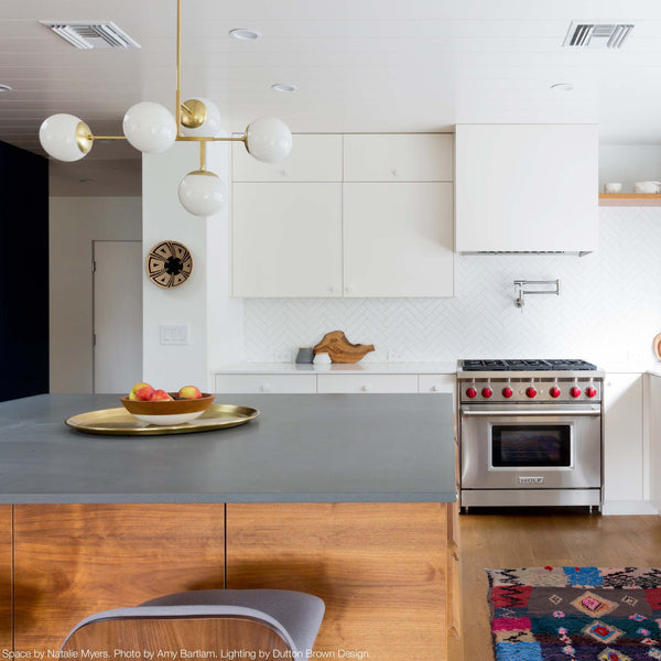 Brass Prisma Globe Chandelier White Globes Kitchen Island Scene. Space by Natalie Myers. Photo by Amy Bartlam. _hover