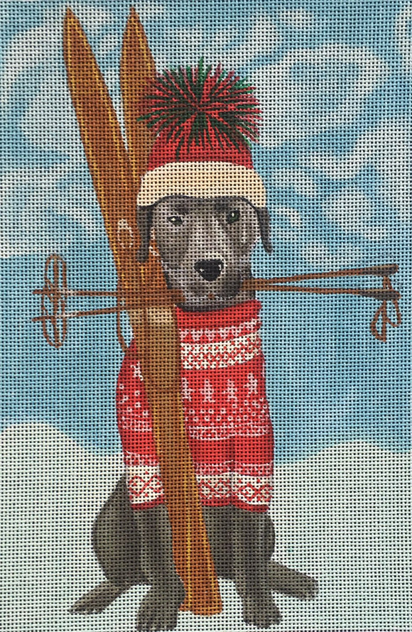Fab Funky whimsical needlepoint canvas of a black labrador dog wearing a fair isle sweater and a beanie with skis and ski poles in the snow