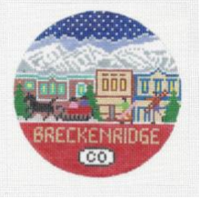 Round needlepoint canvas of Breckenridge Colorado with landscape in background of town and snowy mountains