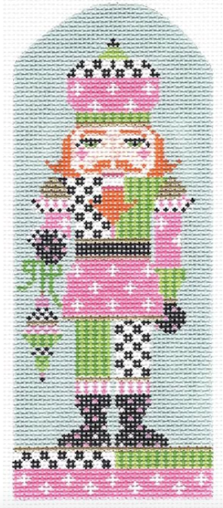 Kelly Clark needlepoint canvas of a preppy nutcracker with pink and green geometric patterns holding a Christmas ornament