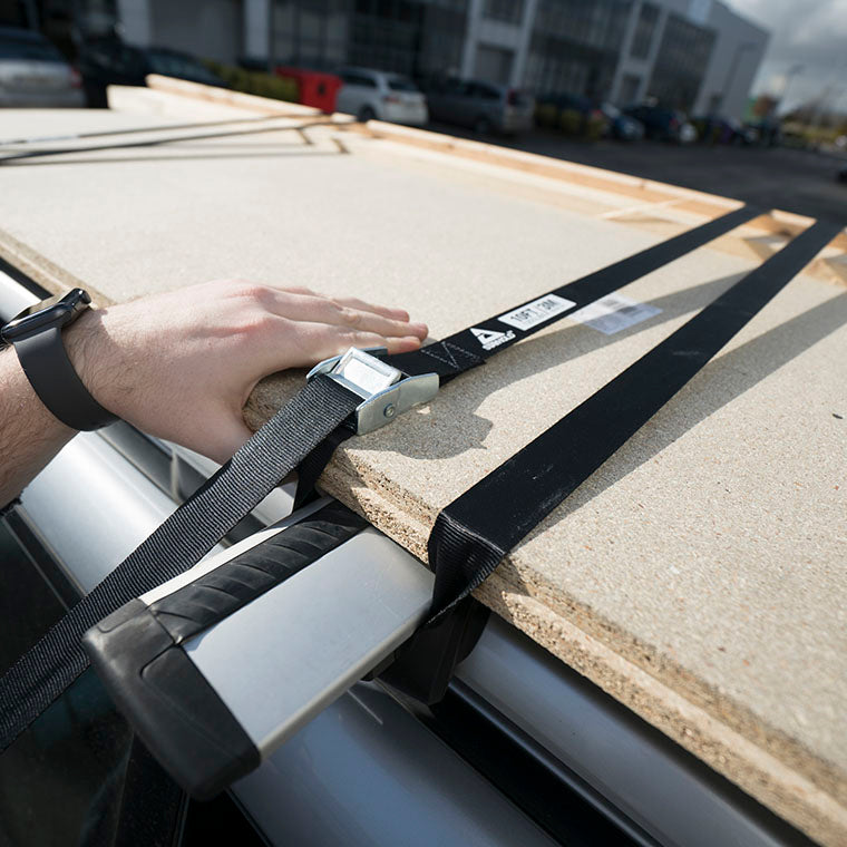Stayhold cargo strap being tightened to hold timber sheets on car roof rack.