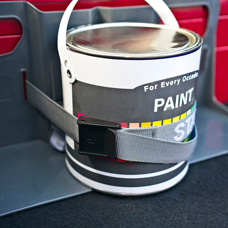 a Stayhold utility strap with plastic buckle being used to secure a tin of paint in a car trunk