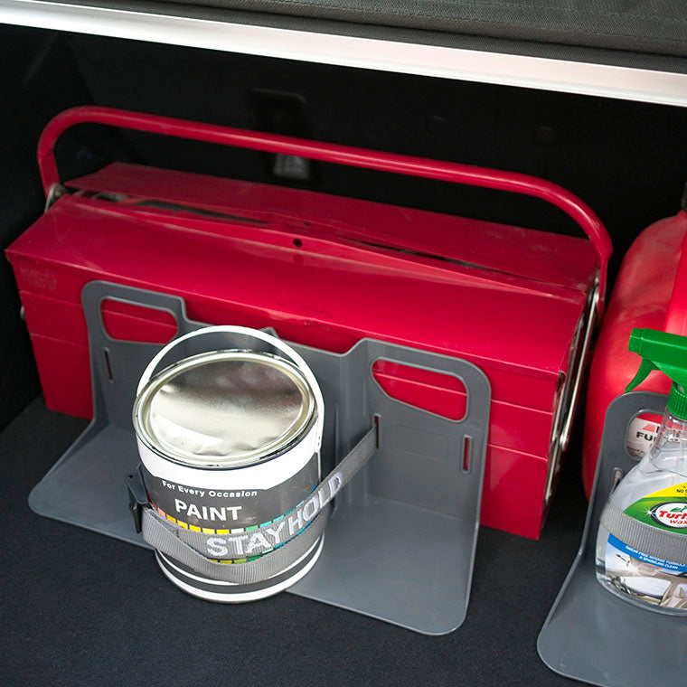 Stayhold cargo holder for carpet holding a toolbox with a can of paint strapped down securely.