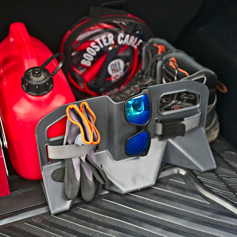 Stayhold cargo holder for suv liners holding shoes, fuel can and booster cables. Also has straps holding gloves and some stylish sunglasses are clipped over the top of the unit.