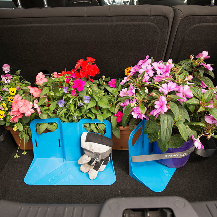 two Stayhold cargo holders and straps holding potted plants and gardening gloves in the back of a car